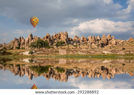 Hot air balloon flying over spectacular Cappadocia (Not a real situation) - stock photo