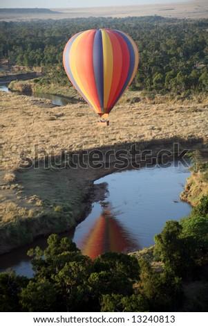 Hot Air Balloon hovers over the winding Mara River in the Masai Mara Reserve (Kenya) - stock photo