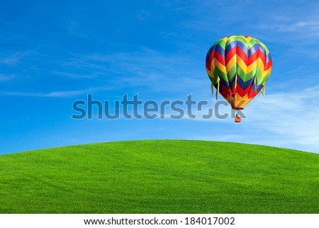 Hot air balloon over green field with blue sky - stock photo