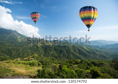 Hot air balloon over mountain landscape - stock photo