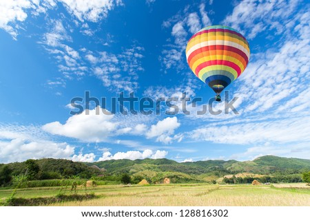 Hot air balloon over the field - stock photo