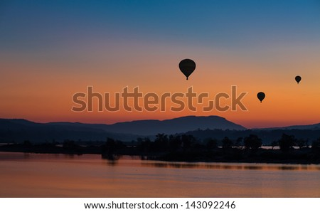 Hot air balloon over the mountain at sunset