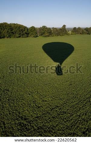 Hot air balloon shadow on field. - stock photo