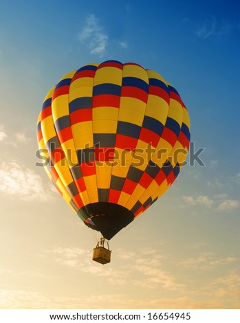 Hot air balloon soaring in early morning - stock photo