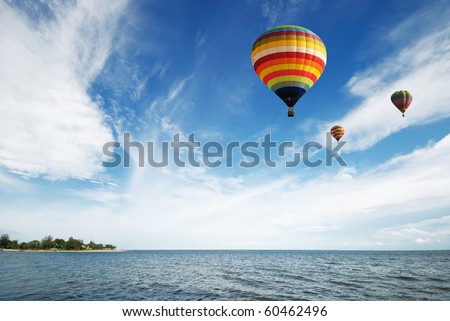 Hot air balloon travel over the sea - stock photo