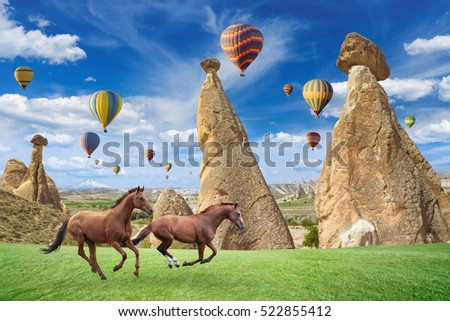 Hot air ballooning is most popular attraction in Kapadokya. Two horses running on green grass near mushroom mountains in Cappadocia, Turkey.