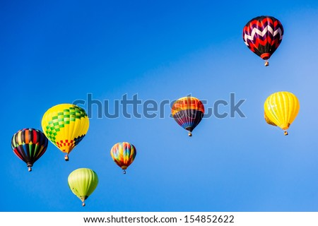 Hot air balloons brighten the blue morning sky in a colorful display of lighter than air flight