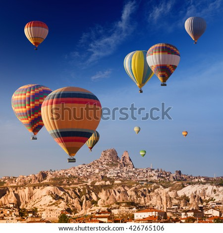 Hot air balloons flying near Uchisar castle in ancient town of Cappadocia, Turkey  - stock photo