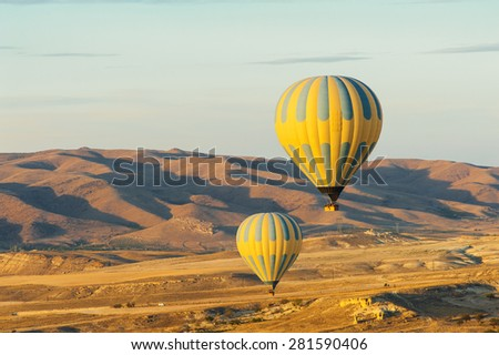 Hot air balloons flying over Cappadocia near Goreme at sunrise, Turkey - stock photo