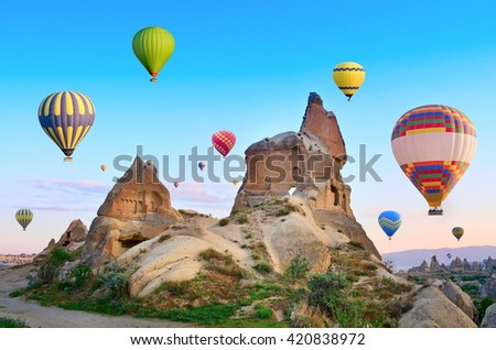 Hot air balloons flying over spectacular landscape of fairy chimneys carved in volcanic tuff by erosion. Cappadocia, Turkey