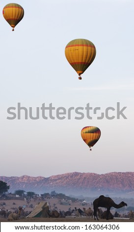 Hot air balloons over Pushkar Camel Fair ground, Pushkar, Ajmer, Rajasthan, India - stock photo