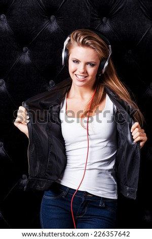 Hot and cheeky. Beautiful young woman in headphones posing against black background - stock photo