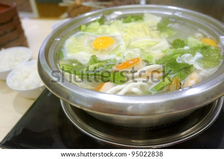 Hot and delicious Chinese fondue or steamboat set in shallow depth of field. - stock photo