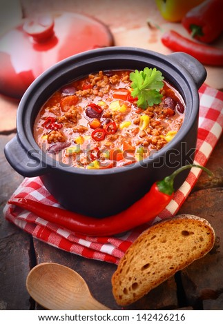 Hot and spicy fresh made Mexican chili still in an iron pot, with a raw chili-pepper and a slice of bread - stock photo