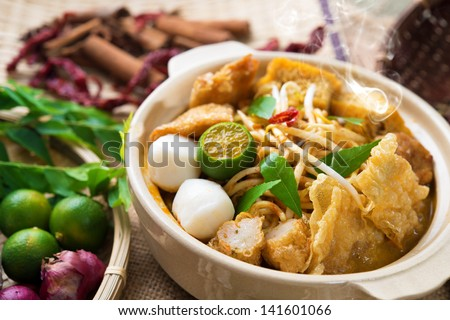 Hot and spicy Malaysia Curry Noodle or laksa  mee with hot steam in clay pot, decoration setup, serve with chopsticks. Malaysian cuisine. - stock photo