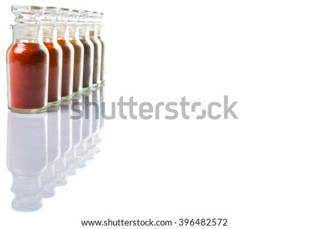 Hot and spicy spices powder, cayenne powder, chilly powder, peppercorn powder, paprika powder, black pepper and white pepper powder in glass vial over white background - stock photo