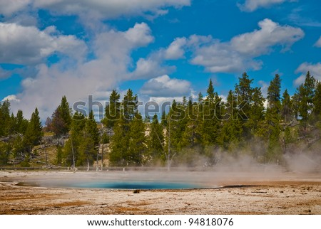 Hot and steamy yellowstone geyser against bright blue cloudy sky
