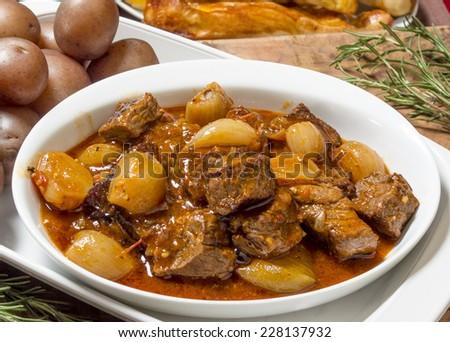 "hot and tasty bowl of greek beef stifado served with baby potatoes and fresh bread sticks  ""Greek beef Stifado"" - stock photo"