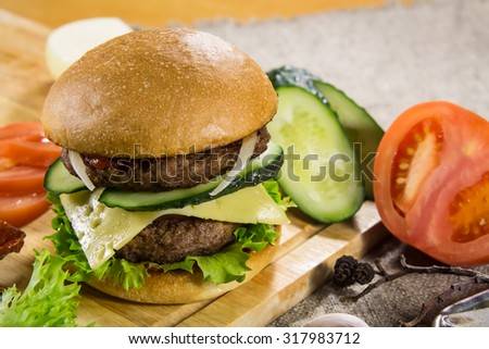 Hot BBQ burger with meat, cheese and vegetables on the cutting board