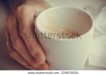 Hot beverage. Closeup woman senior hand holding cup of coffee drinking - stock photo