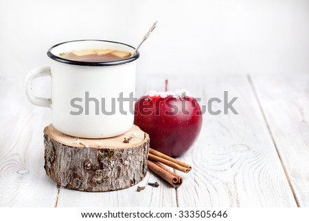 Hot beverage from apples and spices on white wooden background at Christmas time - stock photo