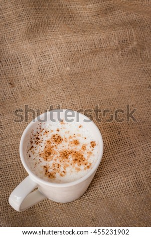 Hot beverage with cinnamon on sackcloth background with copy space
