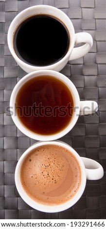 Hot beverages of tea, chocolate and black coffee on a woven place mat - stock photo