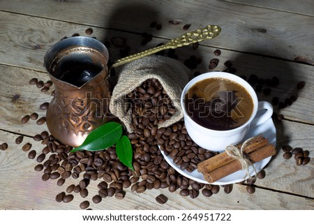 Hot Black Coffee in Coffee Pot and White Coffee Cup with Cinnamon and Coffee Beans in Jute Bag on Wooden Table - stock photo