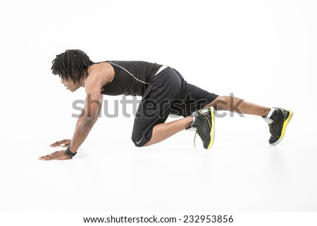 Hot black man with dreadlocks working out wearing all black vest top and exercise shorts in the press up position with one leg bent from the side - stock photo