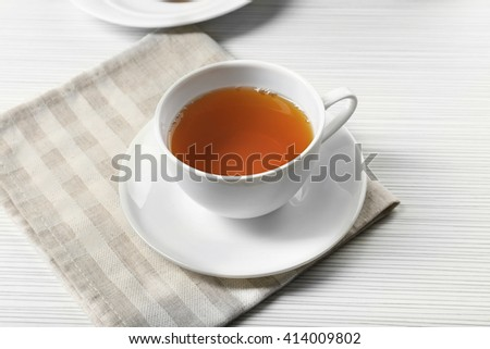 Hot black tea in a cup on a napkin - stock photo