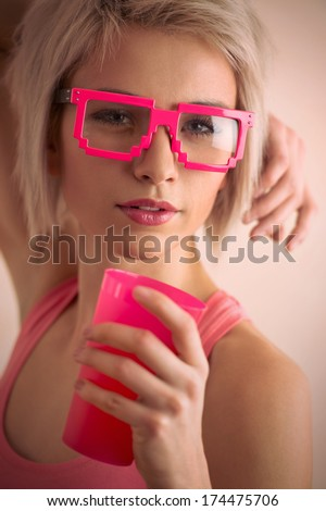 Hot blond girl with short hair wearing freak glasses holding plastic cup and looking at camera - stock photo