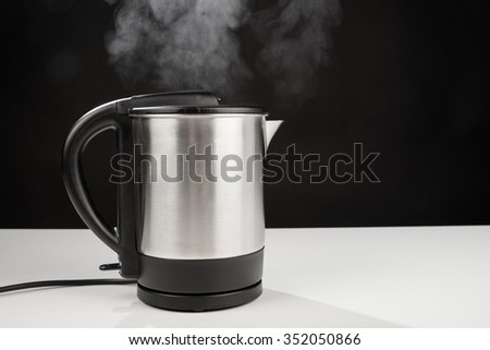 Hot boiling kettle letting out some steam - stock photo