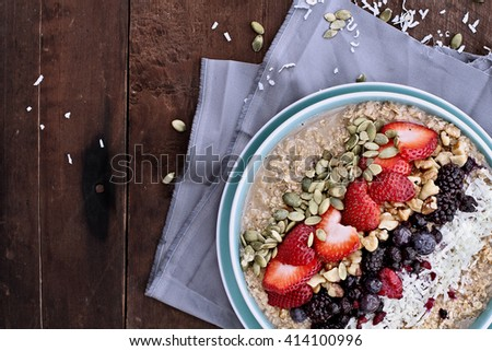 Hot breakfast of healthy oatmeal with shredded coconut, blackberries, blueberries, walnuts, heart shaped strawberries and pumpkin seeds over a rustic background. Image shot from overhead. - stock photo
