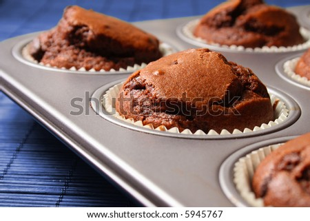 Hot brown muffins on baking tray - stock photo