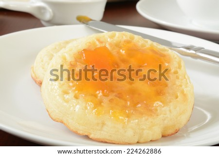Hot buttered crumpets with apricot or peach jam - stock photo