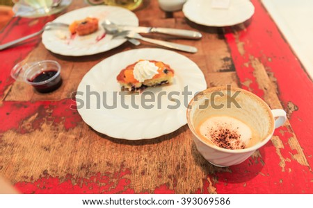 Hot cappuccino coffee cup and piece of cake on table - stock photo