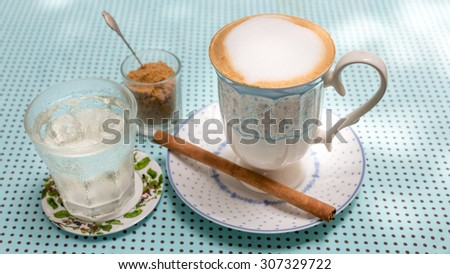 Hot cappuccino coffee in vintage style mug with brown sugar and a glass of water on blue cloth. - stock photo