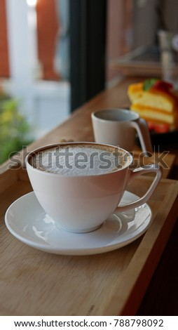Hot  cappuccino Cup of coffee. Sponge cake with Mandarin orange sauce. Sweet and sour refreshing. Place the cake on a plate. Garnish with strawberry flesh fresh. The cake served with coffee.