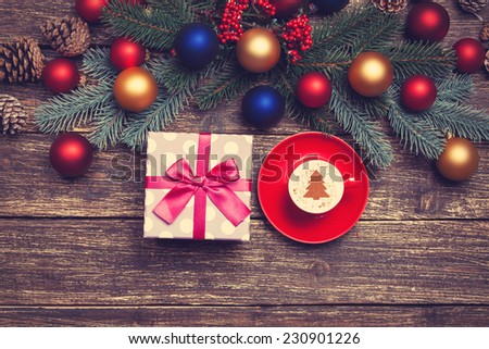 Hot cappuccino with christmas tree shape on a wooden table near pine branches - stock photo