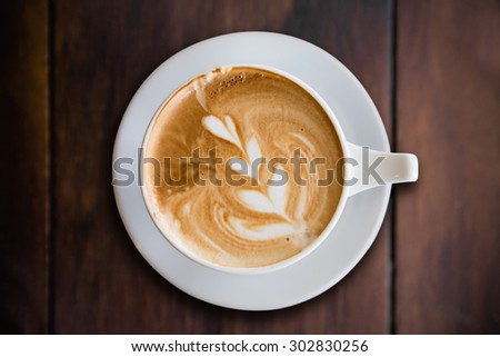 hot cappuccino with latte art on wood background - stock photo
