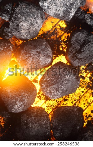Hot charcoal and glowing coals on a barbecue with the grill burning clean to cook the meat and vegetables, full frame background - stock photo