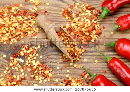 Hot Chili Peppers, Milled  Peppers Flakes and Corns In The Wood Spoon On Rustic Wooden Table Background.  Ingredients for Soup, Salad, Paste - stock photo