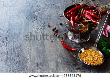 Hot Chili Peppers with herbs and spices on wooden texture - cooking or spicy food concept - stock photo