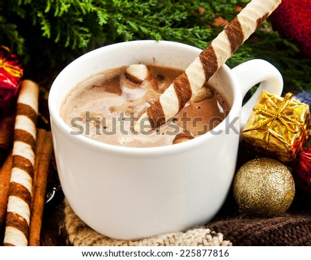 Hot Chocolate Cup with Spiral Snacks and Christmas Decoration in the Background - stock photo