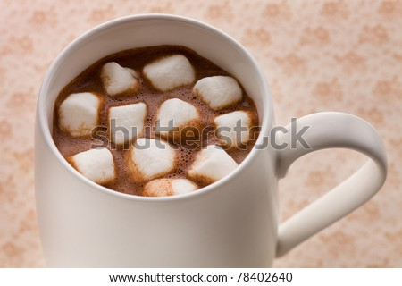 Hot chocolate drink from above on a brown background with marshmallow. - stock photo
