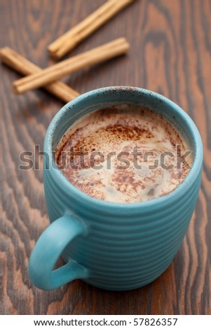Hot chocolate drink with cinnamon sticks on a wooden background - stock photo