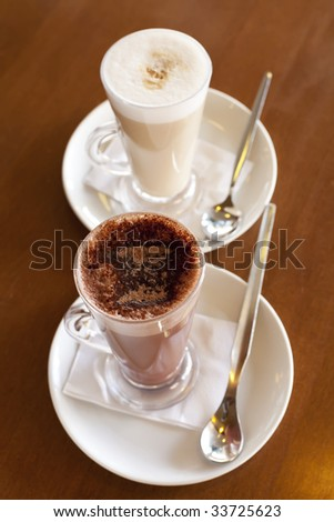 Hot chocolate in a tall class with Cafe Latte on a table, shallow DOF, focus on the cacao top - stock photo