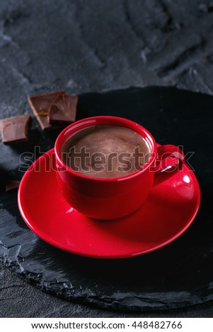 Hot chocolate in red ceramic cup with saucer, served with dark chopped chocolate on round slate stone board over black textured background - stock photo