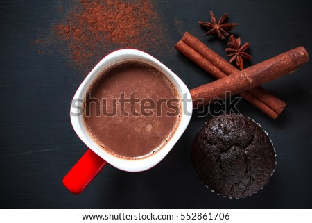 Hot chocolate in red cup with chocolate cup cake on black background, Top view