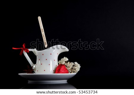 Hot chocolate with candy and flower on black background - stock photo
